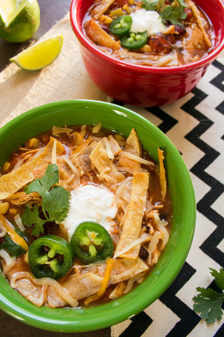 Two bowls of chicken tortilla soup on a counter topped with tortilla strips and jalapeno