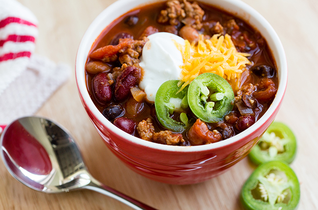 Up close overhead picture of a red bowl filled with turkey chili