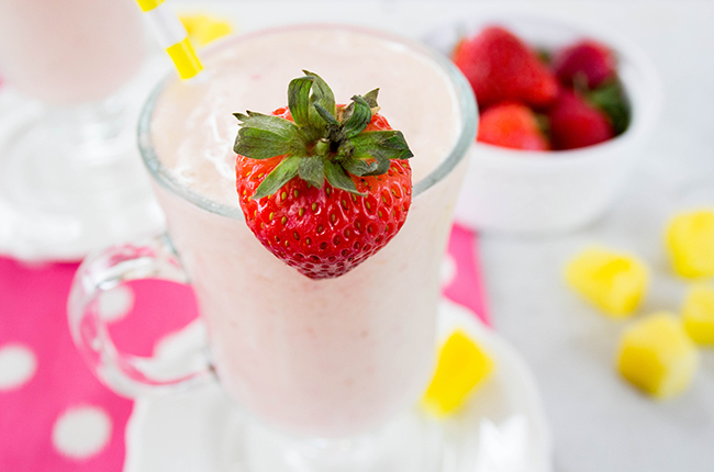Up close picture of a strawberry pineapple smoothie in a tall glass with strawberry garnish