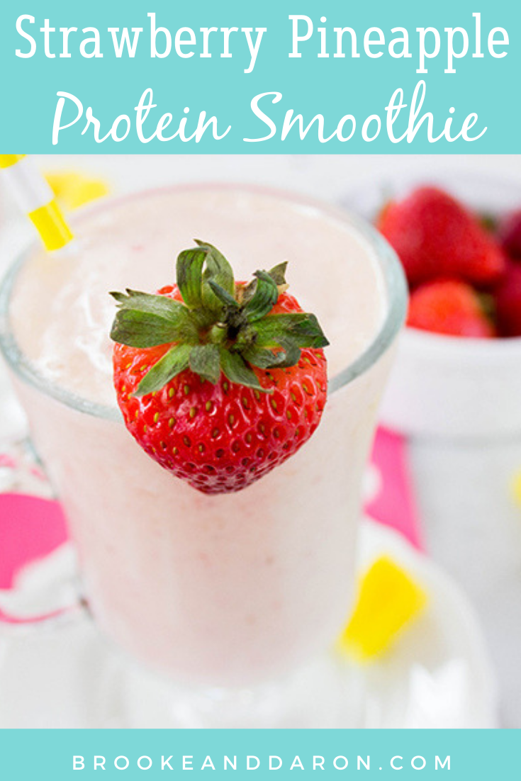 Up close picture of strawberry smoothie with strawberry garnish and pineapple