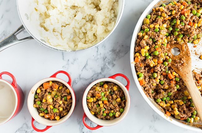 Filling mini crocks with ingredients for shepherds pie recipe