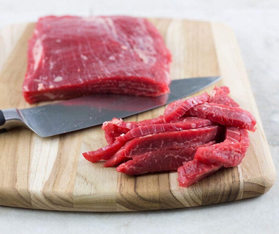 Flank steak on a cutting board being sliced for beef stir fry recipe