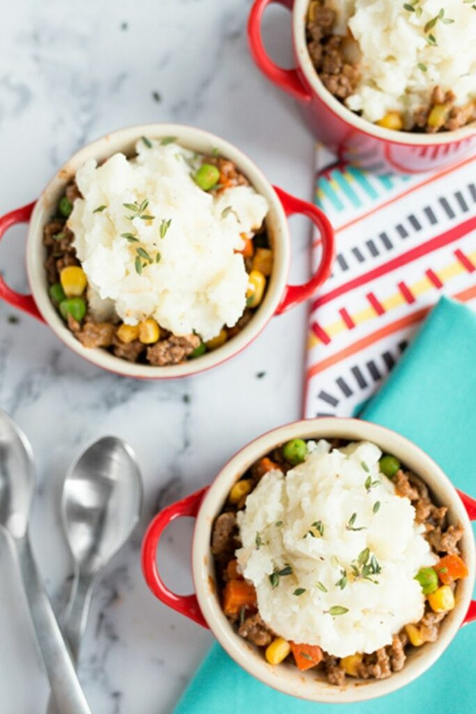 Overhead picture of mini shepherds pies in small red mugs laying on a marble counter