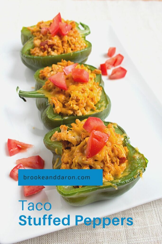 Three bell peppers stuffed with chicken on white plate